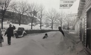 Store fronts with children playing in the snow near Christmas on Jewell Ridge.